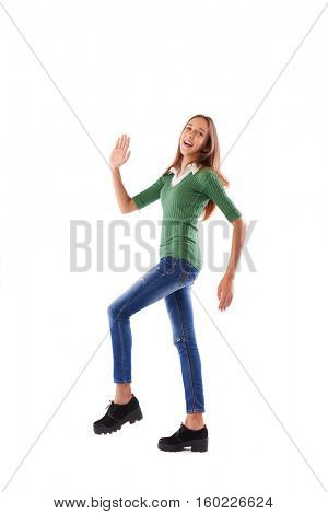 Wide side view shot of joyful and laughing softly teenage taking the first step and waving one hand in studio