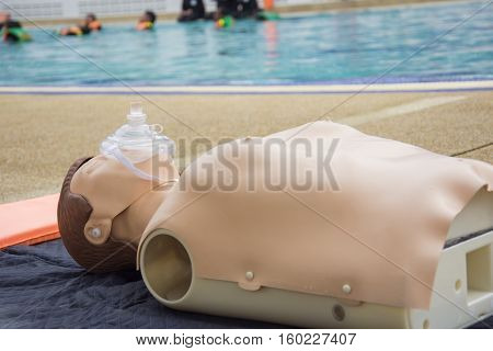 cpr dummy training nearside swimming pool blur background