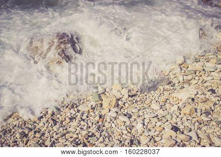 Foamy wave hits pebble rocks on the beach of the Adriatic Sea
