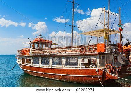 NESEBAR BULGARIA SEPTEMBER 06 2013: Pleasure yacht in the port of the old town of Nessebar. Black Sea coast. Wooden passenger ship standing at the pier. Sunny summer day.