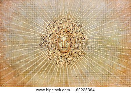 golden sculpture of medusa face on ceiling