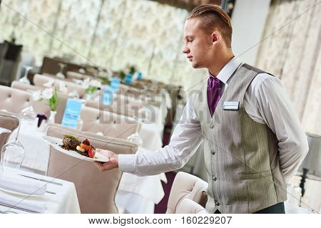 Restaurant waiter serving table with food
