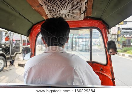 Driver driving tuk tuk - auto rickshaw small vehicle typical for Jakarta Indonesia