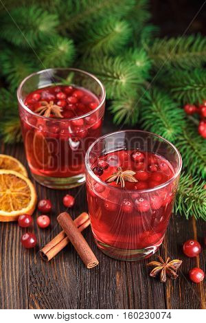 Two glasses of cranberry drink cranberries cinnamon sticks anise stars and dried slices of orange on a wooden background.