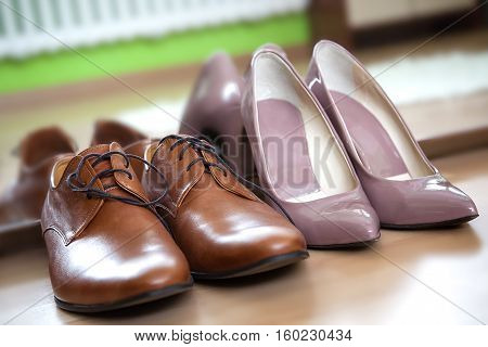 Close up photo of pink latent pointy female heels and male leather camel brown lace up dress shoes placed against mirror on the wooden floor