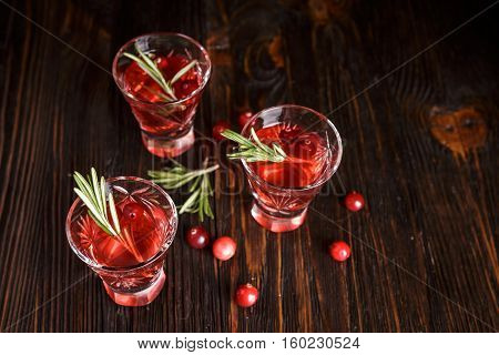 Three glasses of refreshing alcoholic cranberry cocktail with berries cranberries rosemary and spruce branches in the background on a wooden background.