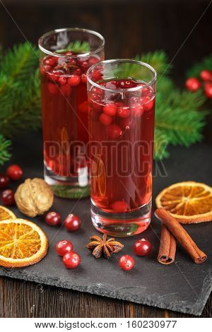 Two glasses with a refreshing cranberry cocktail with berries cranberries rosemary and spruce branches in the background on a wooden background.