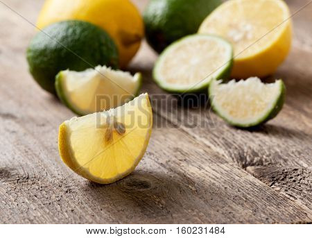 pieces of lemon and lime fresh lemon and lime on a old wooden background