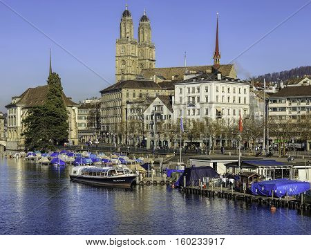 Zurich, Switzerland - 2 December, 2015: the Limmat river and the Limmatquai quay, towers of the Grossmunster Cathedral in the background. Zurich is the largest city in Switzerland and the capital of the canton of Zurich.