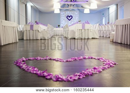pink flower petals heart on wedding dance floor with dining tables covered with white cloth at the background