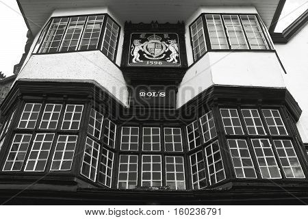 EXETER UK 11 July 2016: Facade of an ancient building in the center of Exeter. Mol`s House 1596. The coat of arms of the city. Black and white photography. Devon. England
