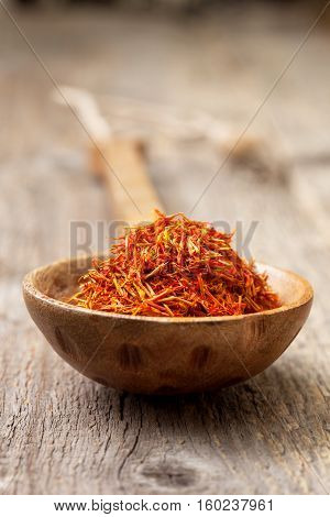 saffron in a wooden spoon on the old wooden background