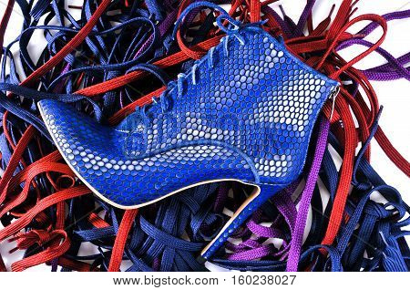Sexy women's shoes on the background of colored laces. Bright blue ankle boots.