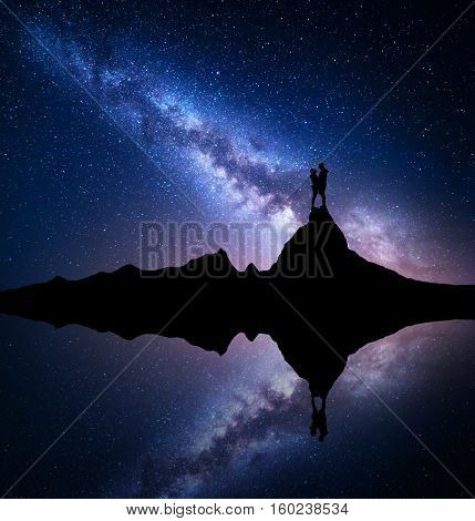 Milky Way. Silhouette of people. Landscape with night starry sky. Standing man and woman on the mountain peak near the lake with sky reflection in water. Hugging couple and milky way. Galaxy. Universe