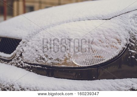 car headlight covered by snow in the morning