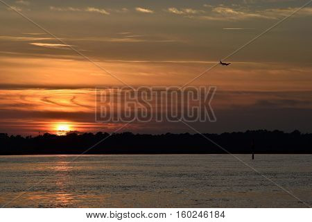 Airplane landing at airport over the river at sunset