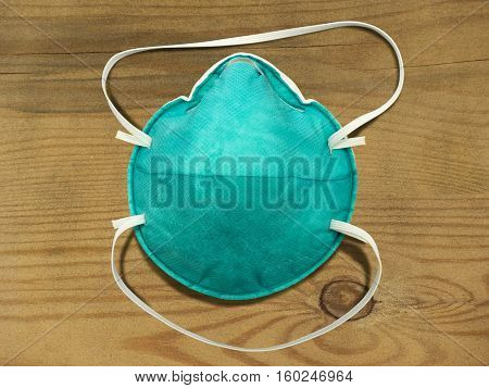 Health care particulate respirator and surgical mask over wooden background.