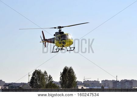 The small yellow helicopter flies in the sky over the city
