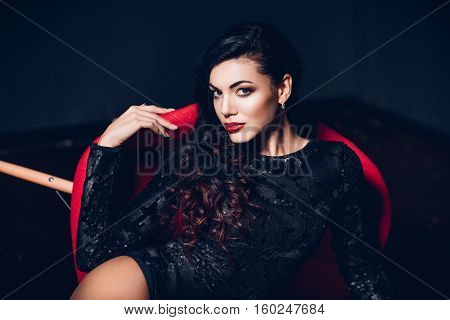 Fashion portrait of young woman wearing seductive lingerie posing in a sensual way in dark room by red modern chair.