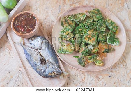 Thai local popular food as spicy shrimp paste dip served with cha-om egg and fired mackarels on wood background