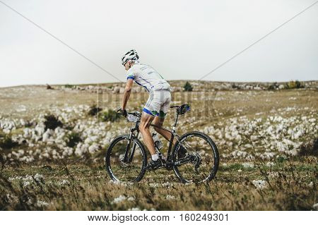 Privetnoye Russia - September 21 2016: male cyclist mountainbiker rides on a mountain landscape during Crimean race mountainbike