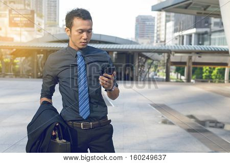 Businessman using mobile phone with city background