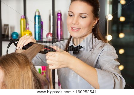 Stylist making curls on woman's head. Horizontal indoors shot