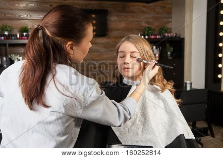 Stylist putting makeup on client's face. Horizontal indoors shot