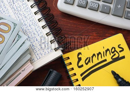 Earnings written in a note, calculator and cash.