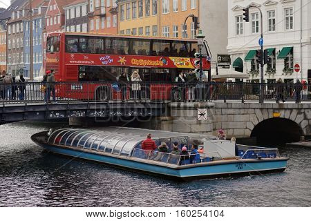 COPENHAGEN, DENMARK - NOVEMBER 5, 2016: Sightseeing bus and tour boat at Nyhavn bridge. Nyhavn is one of the most popular tourist districts in the Danish capital city
