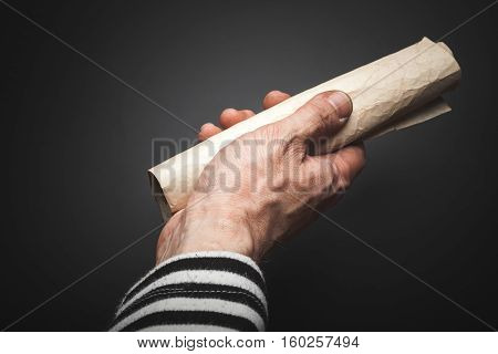 Male Hand Holds Rolled Crumpled Paper