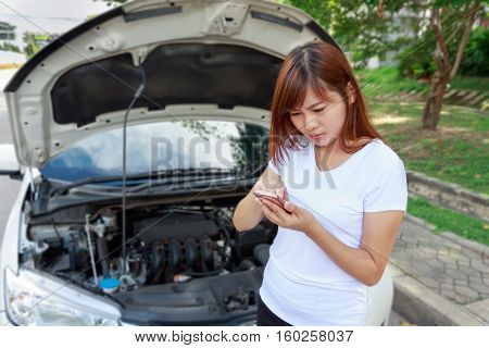 Closeup portrait Stressed woman touching on mobile phone for help on road - car breakdown insurance coverage concept
