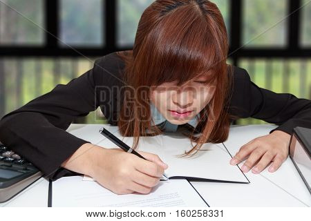 Sleepy and tired business woman at desk holding a pen for writing and close her eyes in office - business concept
