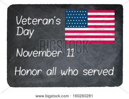 Veteran's Day November 11 written in chalk on a chalky natural slate blackboard isolated against white background