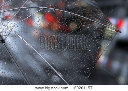 Transparent umbrella with rainy drops close up on street city lights background. 3D illustration
