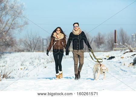 Young couple in love walking with dog outdoors in snowy winter