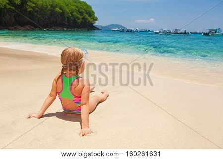 Beautiful little snorkeler relax on sunny white sand ocean beach. Happy baby have fun look at surf in tropic blue lagoon. Active family travel lifestyle water activity on summer vacation with child
