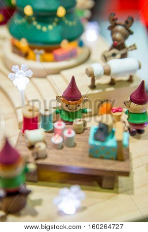 Close-up detail of wooden Christmas toys depicting a scene of elves working in Santa's workshop. Christmas and holidays concept.