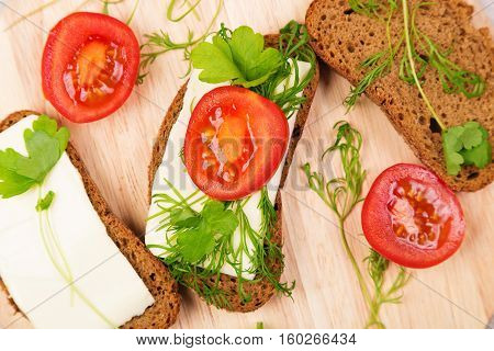 Cheese sandwich parsley dill and tomato on the table.