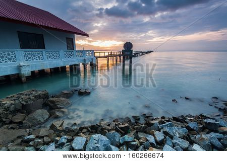 Sunrise by shore with rock foreground for background