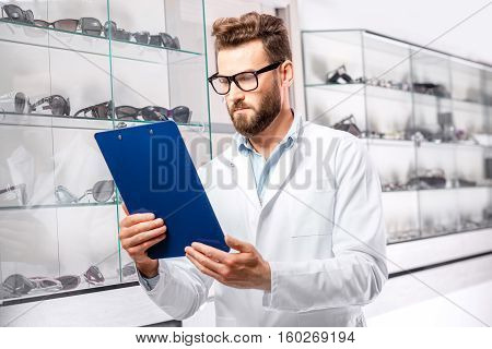 Handsome ophthalmologist with recipe in folder choosing a pair of eyeglasses. Optometrist checking the showcase with glasses in a the store or hospital.