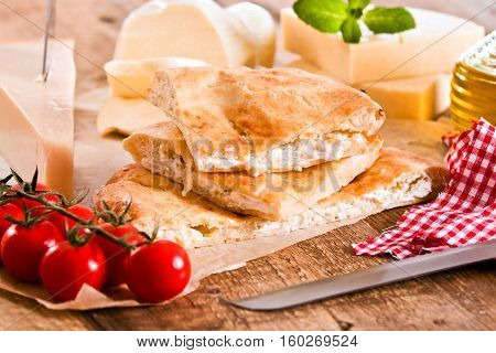 Cheese focaccia bread and other  ingredients on bakign paper.