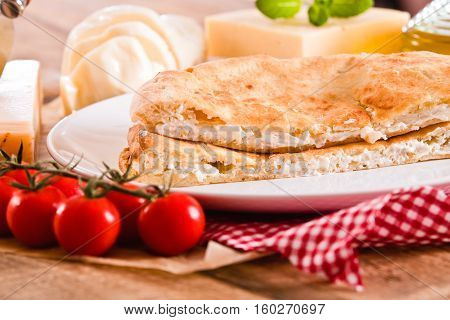 Cheese focaccia bread and other ingrediets on white dish.