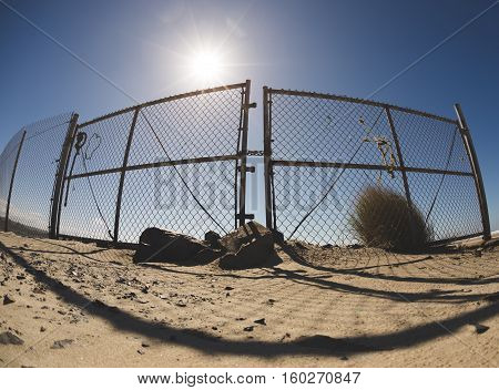 The sun shines bright on a chain link fence, casting a shadow on the foreground. Sunny, summer time, blue sky setting.