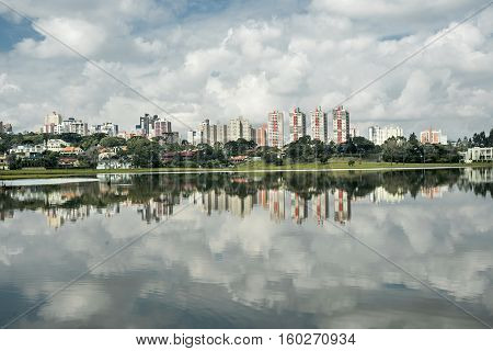 Photography in day with clouds and several buildings reflecting in the lake.