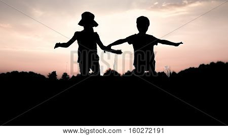 Silhouettes of children jumping off a cliff at sunset. Little boy and girl jump raising hands up high. Brother and sister having fun in summer. Friendship freedom concept. Fraternal twins on vacation in mountains.