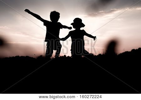 Silhouettes of children jumping off a hill at sunset. Little boy and girl jump raising hands up high. Brother and sister having fun in summer. Friendship freedom concept. Fraternal twins on vacation in mountains.