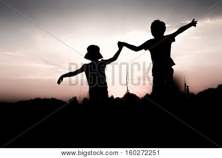 Silhouettes of children jumping off a cliff at sunset. Boy and girl jump high holding hands. Brother and sister having fun in summer. Friendship freedom concept. Twins on vacation in mountains.