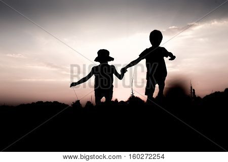 Silhouettes of kids jumping off a hill at sunset. Boy and girl jump high holding hands. Brother and sister having fun in summer. Friendship freedom concept. Twins on vacation in mountains.