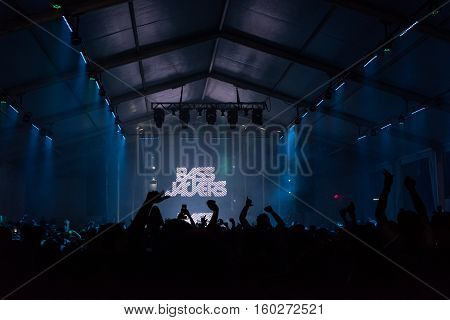 NEW YORK, NY - JUNE 18, 2016: Bassjackers perform at Governors Club on Governors Island, June 18, 2016 in New York City.  Silhouette of fans hands in front of the stage.